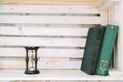 Alte Bücher und Sanduhr liegen auf einem weißen Regal Stockbild