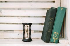 Alte Bücher und Sanduhr liegen auf einem weißen Regal Lizenzfreies Stockbild