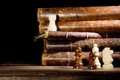 Alte Bücher und Schachfiguren Stockbild