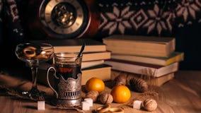 Alte Bücher und Tee am Abend Ein Glas des Getränks auf Tabelle E Stockbilder