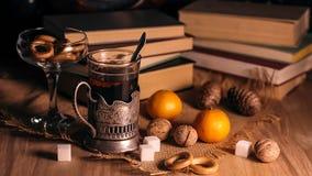 Alte Bücher und Tee am Abend Ein Glas des Getränks auf Tabelle E Lizenzfreies Stockbild