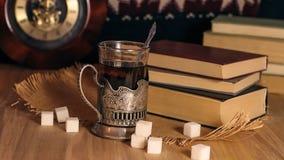 Alte Bücher und Tee am Abend Ein Glas des Getränks auf Tabelle E Stockfoto