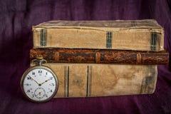 Alte Bücher und Uhr Stockbilder
