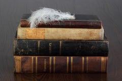 Alte Bücher und weiße Feder Stockfotos