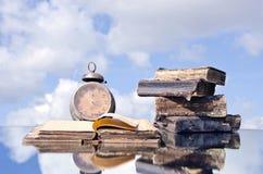 Alte Bücher und Weinleseuhr auf Spiegel Stockbilder