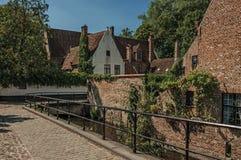 Alte Backsteinhäuser und Grün auf dem Kanal ` s umranden an einem sonnigen Tag in Brügge Stockbild