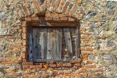 Alte Backsteinmauer Das Fenster oben verschalt mit alten Brettern Lizenzfreie Stockfotografie