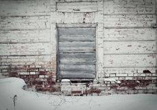 Alte Backsteinmauer in der Mitte des Fensters, gelegter genagelter alter Eber Lizenzfreies Stockfoto