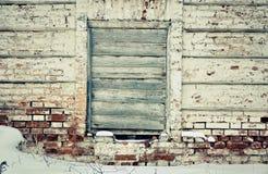 Alte Backsteinmauer in der Mitte des Fensters, gelegter genagelter alter Eber Lizenzfreie Stockfotos