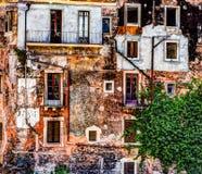 Alte Backsteinmauer der roten Weinlese mit Fenstern und grünem Efeu Lizenzfreie Stockfotografie