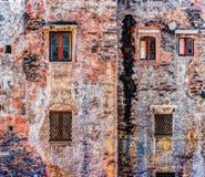 Alte Backsteinmauer der roten Weinlese mit Fenstern und grünem Efeu Stockbild