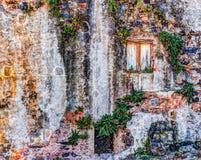 Alte Backsteinmauer der roten Weinlese mit Fenstern und grünem Efeu Stockfoto