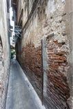 Alte Backsteinmauer der schmalen Straße Lizenzfreie Stockfotos