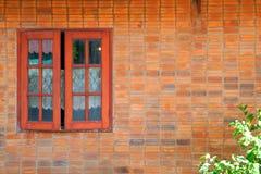 Alte Backsteinmauer des einfachen Hauses der Weinlese und rustikales Außenfenster Stockfotografie