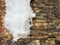 Alte Backsteinmauer des Hintergrundes mit großem Eiszapfen, Beschaffenheit weinlese Lizenzfreies Stockfoto