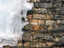 Alte Backsteinmauer des Hintergrundes mit großem Eiszapfen, Beschaffenheit weinlese Stockbild