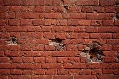 Alte Backsteinmauer des Hintergrundes mit Löchern von Kugeln Stockbilder