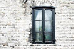 Alte Backsteinmauer des Schmutzes mit schwarzem Fenster Stockfotos