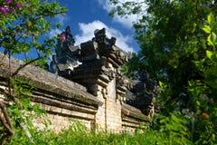 Alte Backsteinmauer eines Balinesetempels unter dem Grün Stockfotos