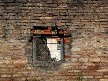 Alte Backsteinmauer eines ruinierten Gebäudes mit einem Fenster Lizenzfreie Stockfotos