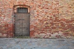 Alte Backsteinmauer, entsteinen gepflasterten Bürgersteig und alte Holztür Lizenzfreies Stockbild