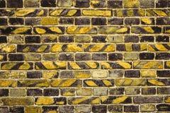 Alte Backsteinmauer für des Hintergrundes, Gelber und Schwarzer Farbe der Beschaffenheit oder Stockfotos