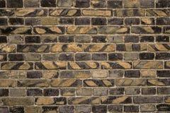 Alte Backsteinmauer für des Hintergrundes, Gelber und Schwarzer Farbe der Beschaffenheit oder Stockbilder