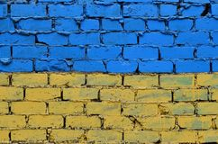Alte Backsteinmauer gemalt in den Farben der ukrainischen Flagge Stockfoto