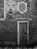 Alte Backsteinmauer mit blockierten Fenstern und Tür Lizenzfreie Stockfotos