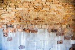 Alte Backsteinmauer mit dem schädigenden Gips Lizenzfreie Stockfotos