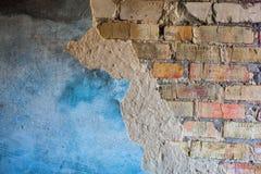 Alte Backsteinmauer mit dem schädigenden Gips Stockbild