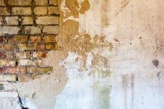 Alte Backsteinmauer mit dem schädigenden Gips Stockfotografie