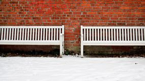 Alte Backsteinmauer mit der zwei Weiß-Bank im Winter Lizenzfreies Stockfoto