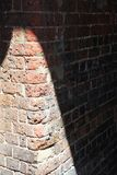 Alte Backsteinmauer mit dunklen Schatten Stockfoto