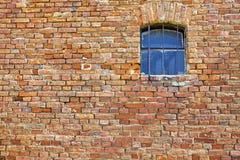 Alte Backsteinmauer mit einem kleinen Fenster Lizenzfreies Stockbild