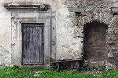 Alte Backsteinmauer mit einer Holztür und ein ruinierter Bogen, eine Beschaffenheit des mittelalterlichen Innenraums Lizenzfreies Stockbild