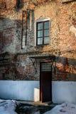 Alte Backsteinmauer mit einer Tür, einem Fenster und Treppe Stockbilder