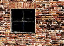 alte Backsteinmauer mit einer zerbrochenen Fensterscheibe Lizenzfreies Stockfoto