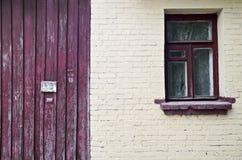 Alte Backsteinmauer mit Fenster und Zaun Lizenzfreie Stockfotos