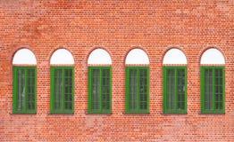Alte Backsteinmauer mit Fenstern Stockbild