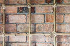 Alte Backsteinmauer mit gebundenem Bambus Stockfotos
