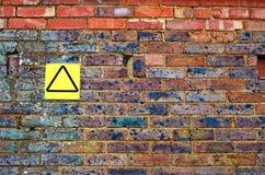 Alte Backsteinmauer mit gelbem Zeichen Lizenzfreie Stockfotos