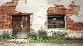 Alte Backsteinmauer mit geschlossener Tür und Gitterfenster Stockbild