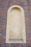 Alte Backsteinmauer mit gewölbter leerer Fensternische Stockbild