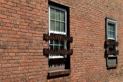 Alte Backsteinmauer mit Gitterfenstern Stockbild