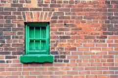 Alte Backsteinmauer mit grünem Fenster Stockfotos