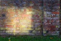 Alte Backsteinmauer mit großer gelber Sonnenstelle Stockfoto