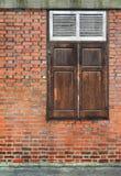 Alte Backsteinmauer mit hölzernem Fenster Lizenzfreie Stockfotos