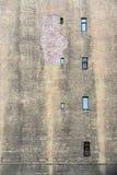 Alte Backsteinmauer mit kleinen Fenstern Stockbilder