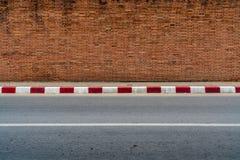 Alte Backsteinmauer mit konkretem Bürgersteig Lizenzfreies Stockbild